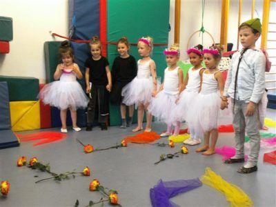 Kleine Ballerinas und Ballerinos stehen im Halbkreis und halten sich an den Händen.