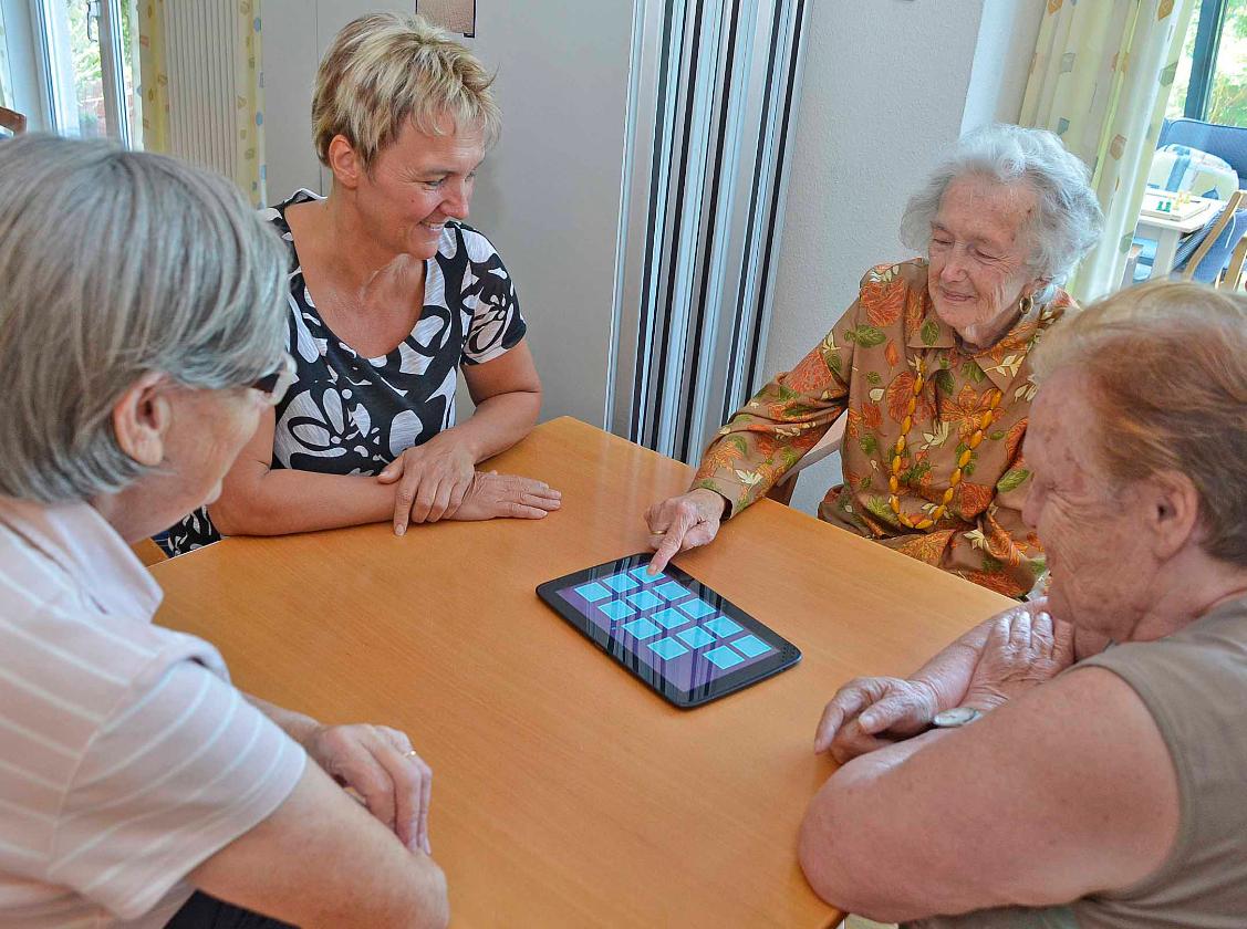 Vier Frauen sitzen an einem Tisch und eine drückt auf den Bildschirm eines Tablets.