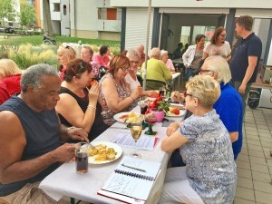 Eine Gruppe von Menschen sitzt an einem langen Tisch und isst zusammen.