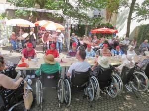 Ein Gruppe von Menschen sitzt an einem langen Tisch im Freien.