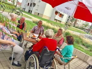 Eine Gruppe Senior*innen sitzt an einem Tisch auf einer Terrasse.