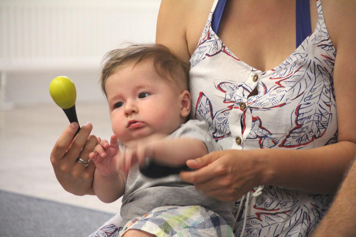 Ein Baby liegt im Arm einer Frau und hält eine Rassel fest