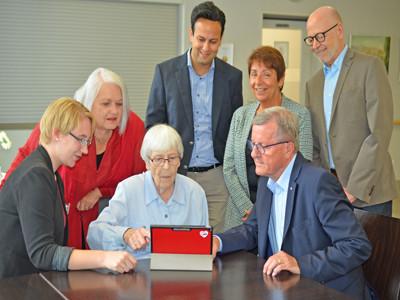 Eine Gruppe von Menschen sitzt an einem Tisch und testet einen Tablet PC.