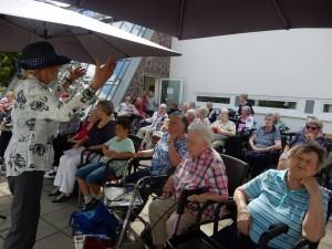 Eine Frau steht vor einer Gruppe Menschen auf der Terrasse vom Hanne-Landgraf-Haus und singt.