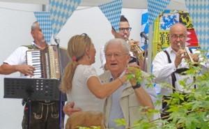 Ein Mann und eine Frau tanzen zu bayrischer Live-Musik.