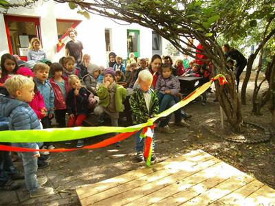 Kinder schneiden ein Band in einem Garten durch.