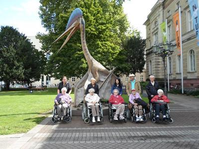 Eine Gruppe von Senioren sitzt in Rollstühlen vor dem Naturkundemuseum.
