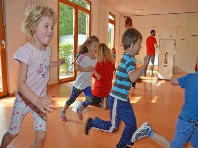 Kita Kinder rennen durch die Turnhalle.