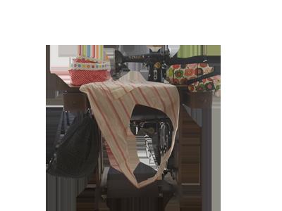 Bild von einer Nähmaschine mit Schürze und Tasche.