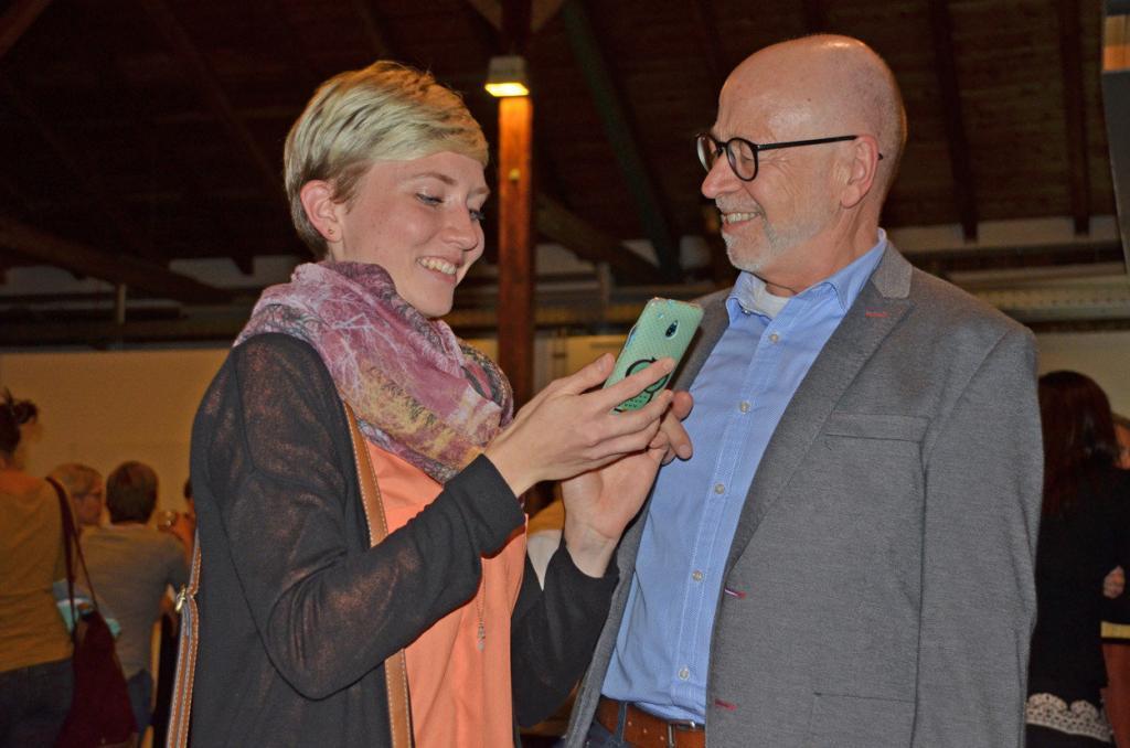 Ein Mann und eine junge Fraue schauen zusammen auf ein Handy.