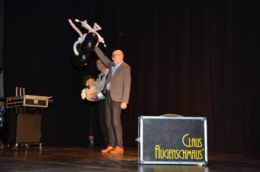 Ein Mann steht auf einer Bühne und hält einen rosaroten Panther aus Luftballons in die Luft.