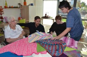 Ein Mann und drei Damen schauen sich bunte Wolldecken an, die auf einem Tisch liegen.