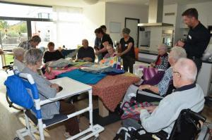 Eine Gruppe von Senioren und ihren Helfern sitzen an einem Tisch und schauen sich bunte Wolldecken an.