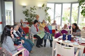 Eine Gruppe von Senioren und ihre Betreuer schauen sich bunte Wolldecken an.