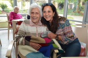 Zwei Frauen lächeln fröhlich in die Kamera.