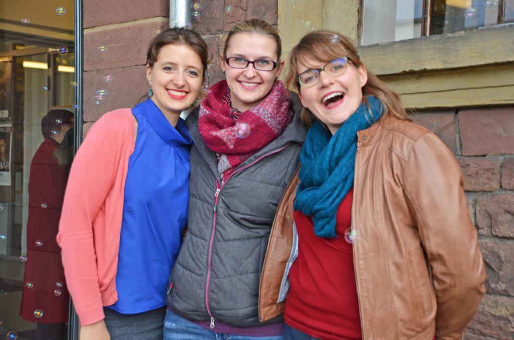 Drei junge Frauen lächeln in die Kamera.
