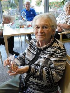 Eine Frau hält ein Brezel in den Händen.