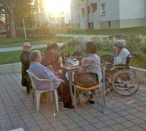 Eine Gruppe von Menschen sitzt an einem Tisch auf einer Terrasse.