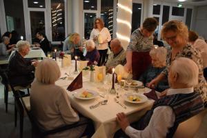 Menschen bedienen andere Menschen, die an Tischen sitzen.