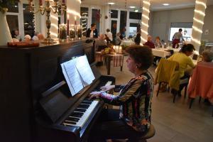 Eine Frau sitzt am Klavier und spielt für ein paar Menschen, die an Tischen sitzen.