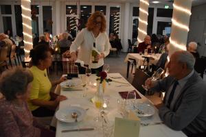 Eine Frau steht vor einem Tisch und schenkt Wein ein.