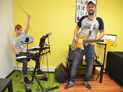 Ein kleiner junge sitzt am Schlagzeug, ein Mann mittleren Alters steht danaben an der E-Gitarre.