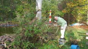 Ein Mann steht im Grünen und gräbt Erde um.