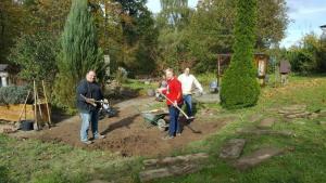 Drei Menschen stehen auf einem Beet und graben die Erde um.