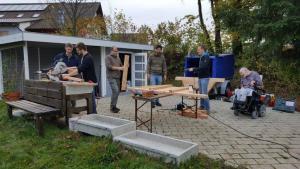 Eine Gruppe von Menschen arbeitet mit Holzplatten.