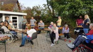 Eine Gruppe von Menschen steht und sitzt zusammen und feiert.