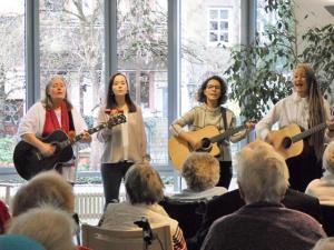 Vier Frauen Singen und spielen Gitarre