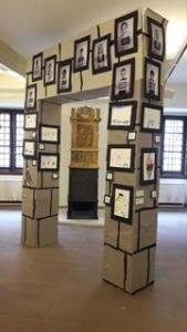 Schwarze Rahmen mit Bildern hängen an einer Säule an der Wand.