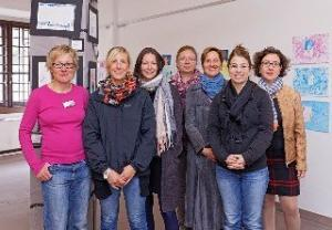 Eine Gruppe von Frauen posiert vor Bildern an der Wand.