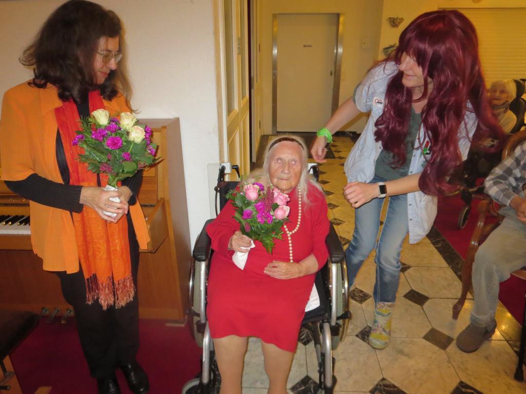Eine Seniorin sitzt im Rollstuh, neben ihr stehen zwei Frauen mit Blumen in den Händen.