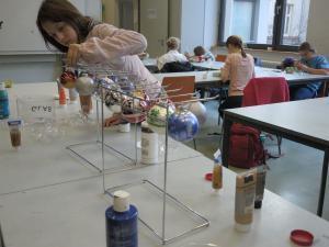 Ein Mädchen hängt bemalte Glaskugeln zum Trocknen auf.