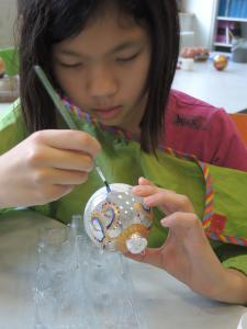 Ein Mädchen bemalt eine Glaskugel.