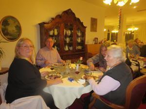 Menschen sitzen an einem Tisch und essen zusammen.