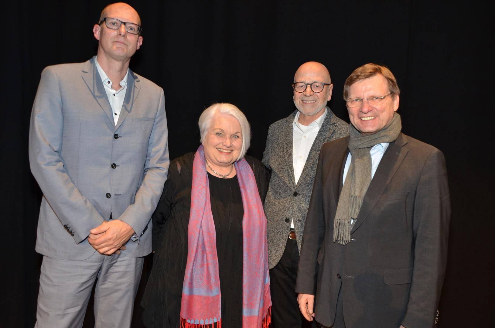 Drei Männer und eine Frau stehen vor einem schwarzen Vorhang.
