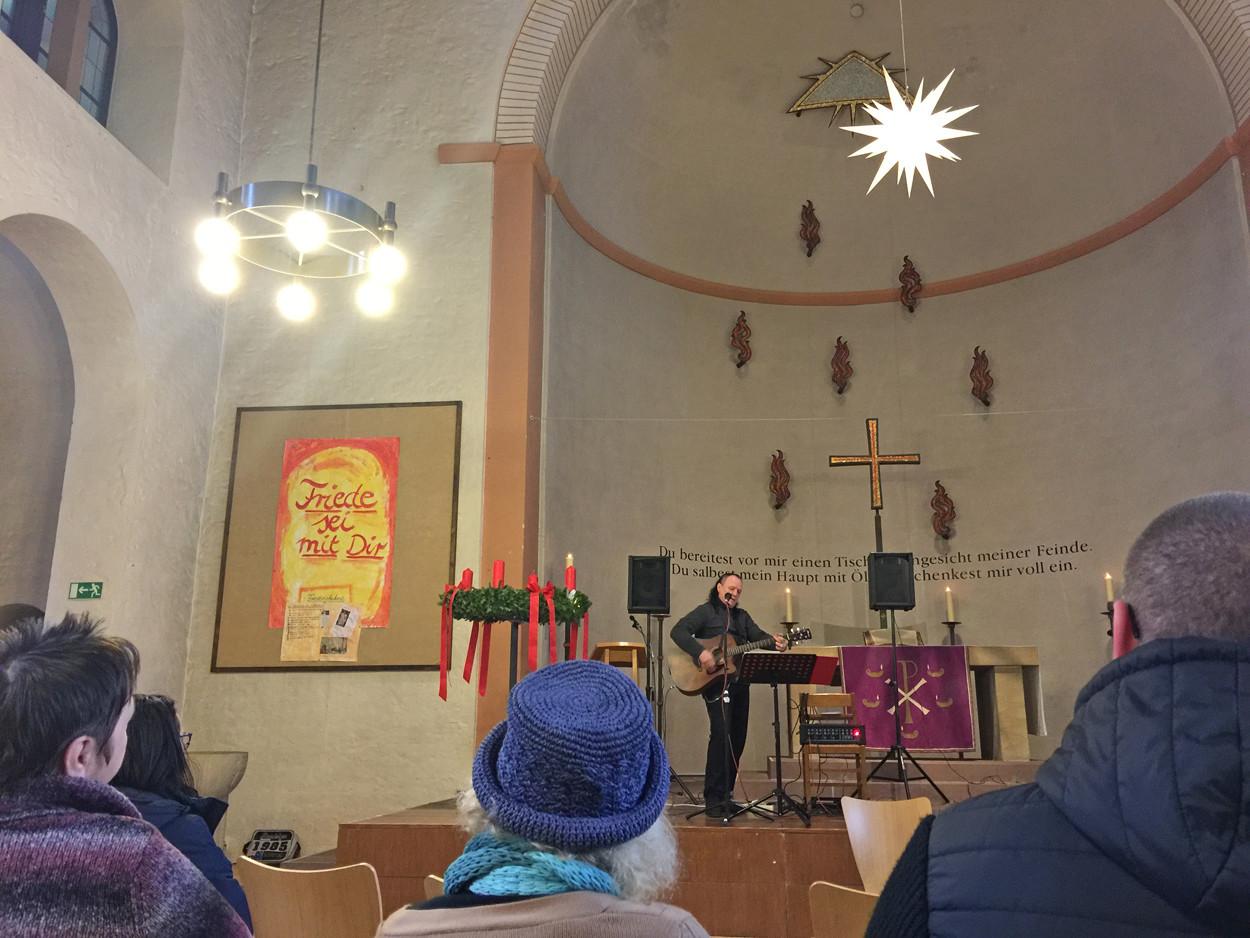 Ein Mann steht in einer Kirche und spielt Gitarre.