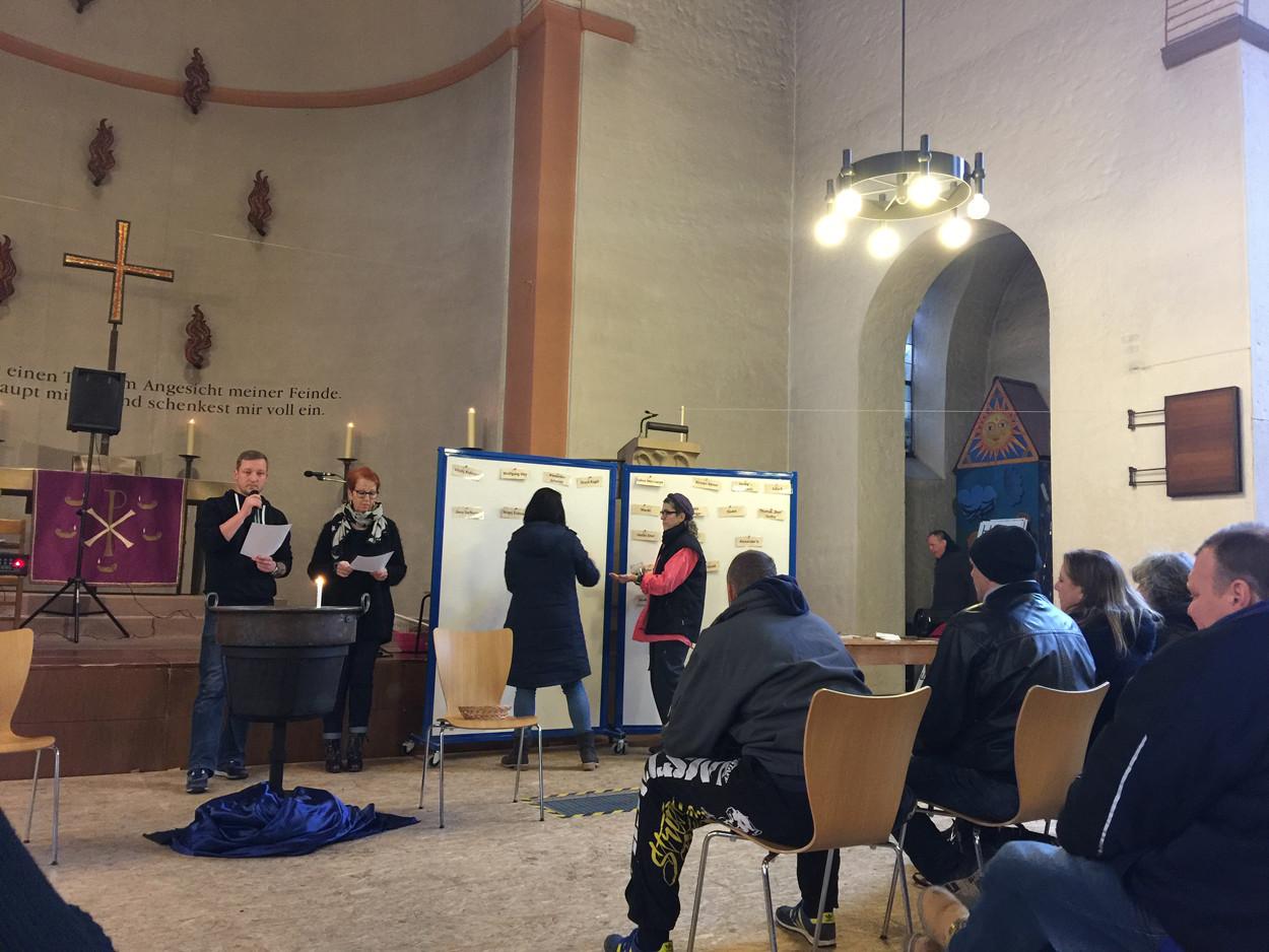 Menschen in einer Kirche heften Zettel mit Namen an eine Pinnwand.