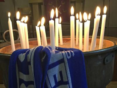 Ein Tisch mit Kerzen und KSC Schal.