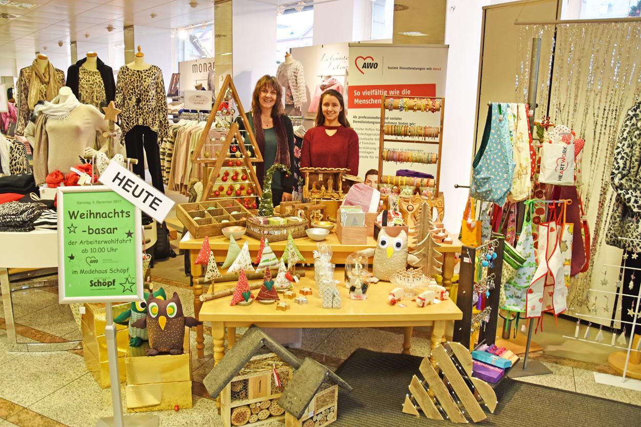 Zwei Frauen stehen an einem Stand und verkaufen handgefertigte Waren.