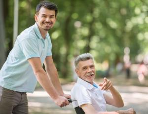 Ein junge Mann schiebt einen Senior im Rollstuhl durch einen Park.