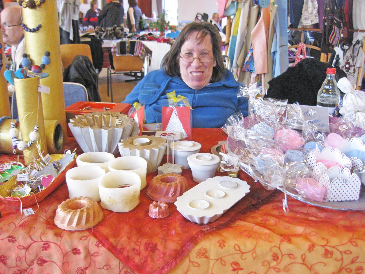 Eine Frau im Rollstuhl sitzt an einem Stand und verkauft handgefertigte Waren.