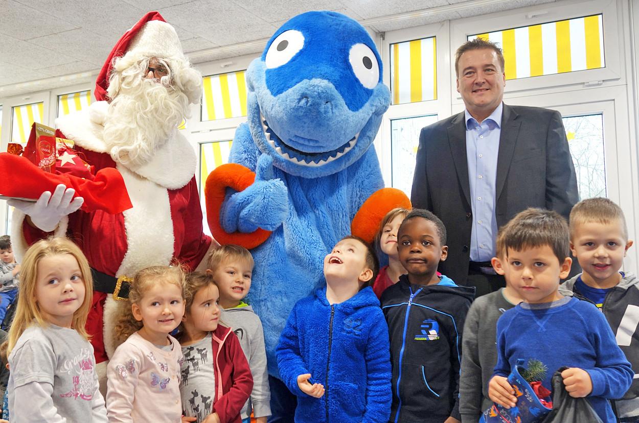 Eine Gruppe von Kindern steht mit einem Nikolaus und einer Hai-Figur im Halbkreis.