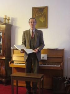 Ein Mann steht vor einem Klavier.