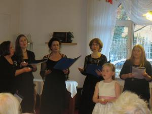Vier Frauen und ein Kind stehen vor Menschen und singen.