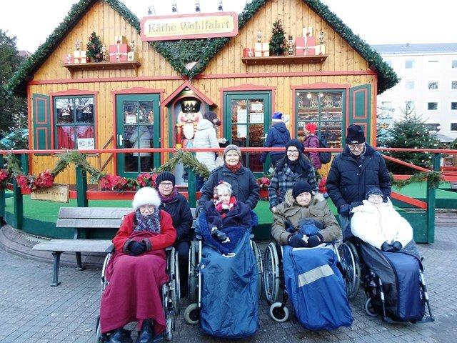 Eine Gruppe von Senior*innen sitzt in Rollstühlen auf dem Weihnachtsmarkt.