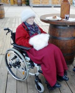 Eine Seniorin sitzt im Rollstuhl an einer Glühweinbude.