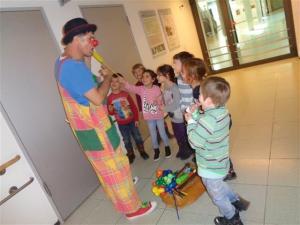 Kinder der AWO Kita les petits amis stehen um einen Clown herum und lachen.
